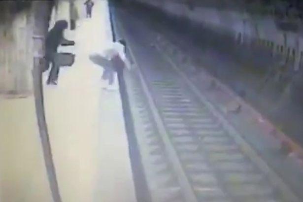sumasshedshaya-tolknula-moloduyu-zhenshhinu-v-metro-pod-poezd-video